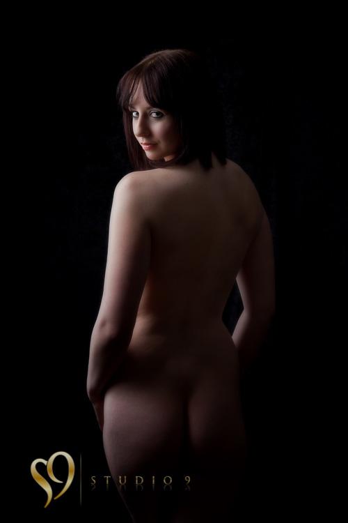 Beautiful standing nude figure looking over shoulder.