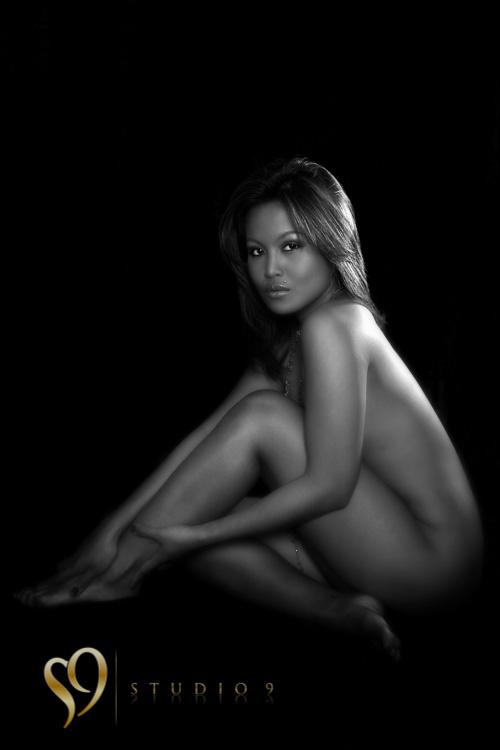 Beautiful seated fine art pose of lady in studio.